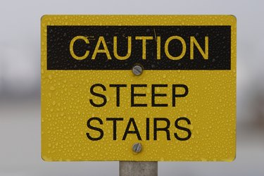 Scratched steep stairs warning sign