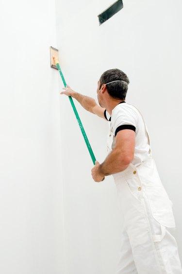 Construction worker using pole sander