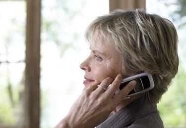 Mature woman using mobile phone, profile, close-up