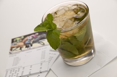 Beverage with mint leaves and horseracing wager cards