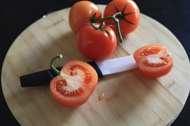 Ceramic knife and red tomatoes on cutting board