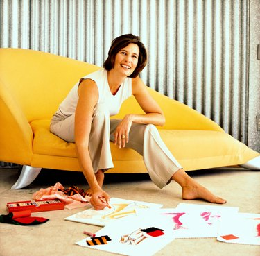 Young woman sitting on a couch drawing fashion designs