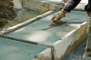 Construction worker smoothing wet concrete with trowel