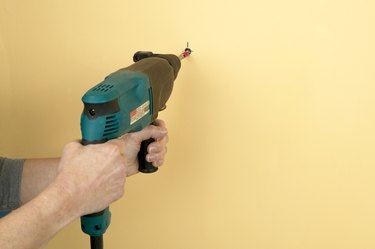 Man using drill to make hole in wall