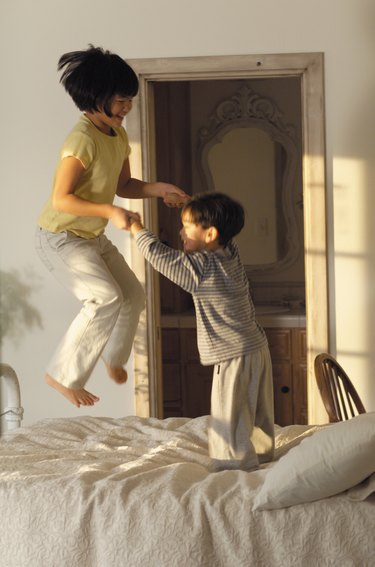 lifestyle photograph of two asian children as they play together and jump on the bed