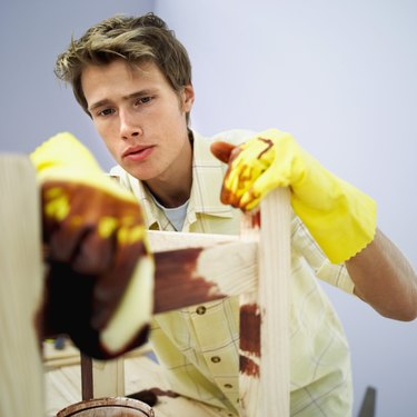Young man applying wood varnish on a wooden chair with a paint brush