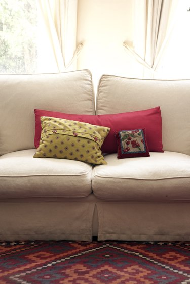 cream sofa with pillows infront of a window