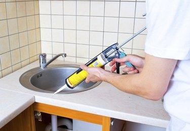 Caulking gun putting silicone sealant to installing a kitchen sink