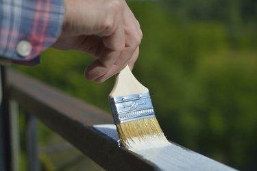 Man painting a guardrail