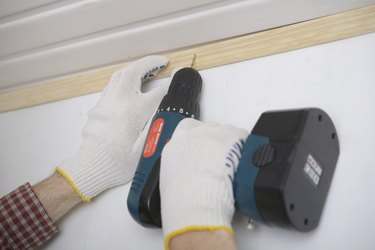 Contractor installing molding to ceiling using cordless power drill