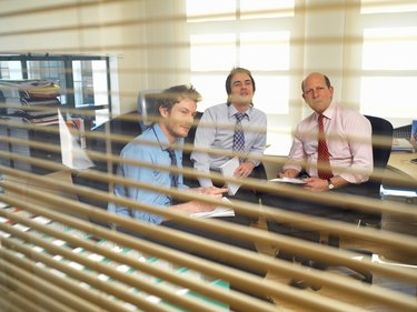 Three businessmen in meeting, view through glass panel