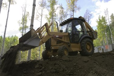 Yellow digger removing debris near forest, low angle view