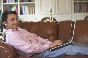 Portrait of a mid adult man lying on a couch working on a laptop