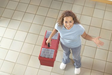Woman Standing on Tile Floor Holding Toolbox