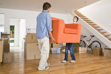 Couple carrying arm chair into new home