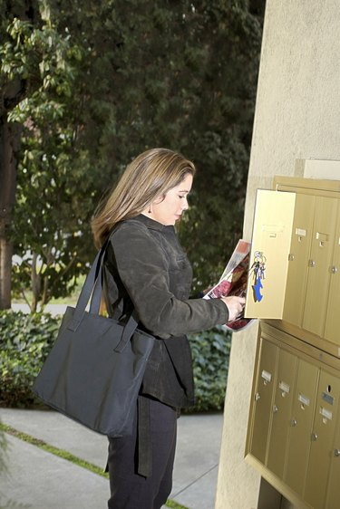 Woman looking in apartment building mailbox