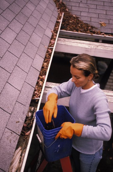 Woman Cleaning out Rain Gutters