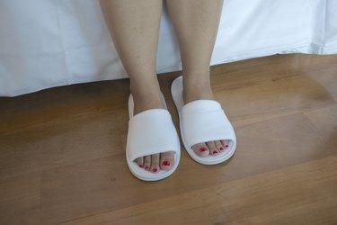 Woman feet with white slipper