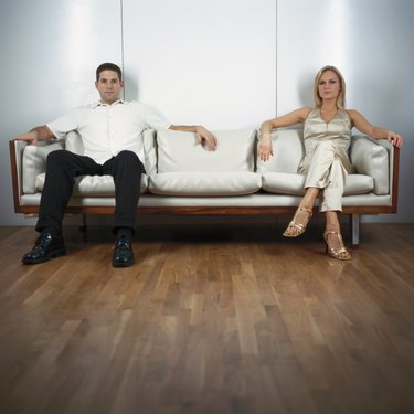 Young couple sitting on sofa, portrait