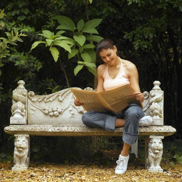 Front view of young woman sitting on bench, reading newspaper
