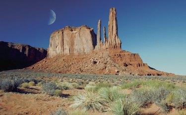 Moon over an arid landscape, Monument Valley Navajo Tribal Park, Arizona, USA