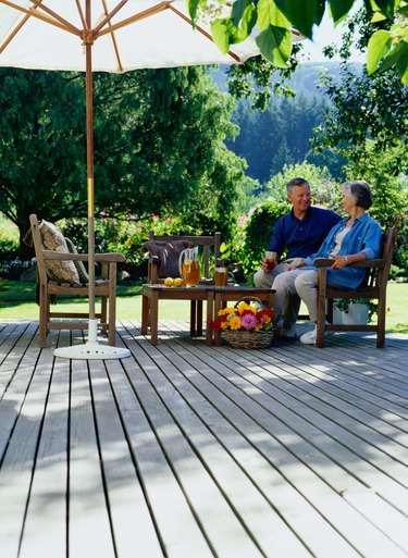 Mature couple sitting on deck drinking iced tea