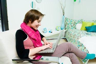Woman using laptop computer in bedroom