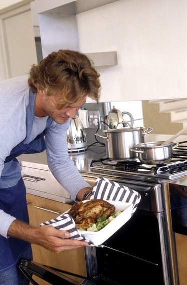Man taking roast chicken from oven