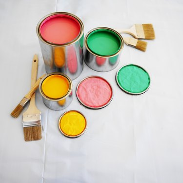 open paint cans and paint brushes on the floor