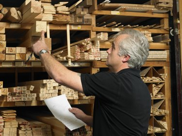 Man selecting plank of wood from shelves, rear view