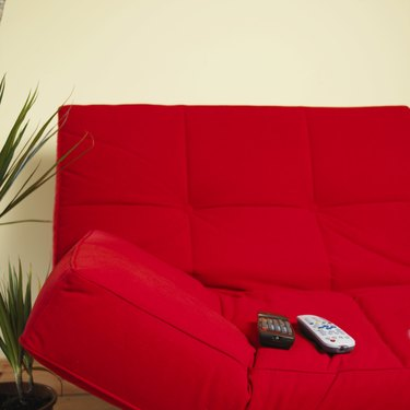 Remote controls on red sofa
