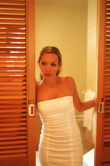 Young woman standing by open door, looking to side