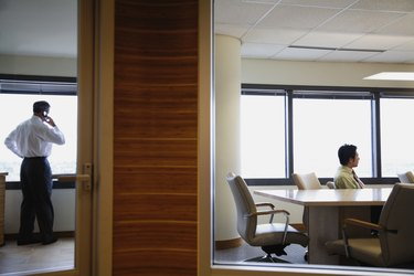 View through window to businesspeople working