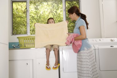 Woman and girl folding laundry