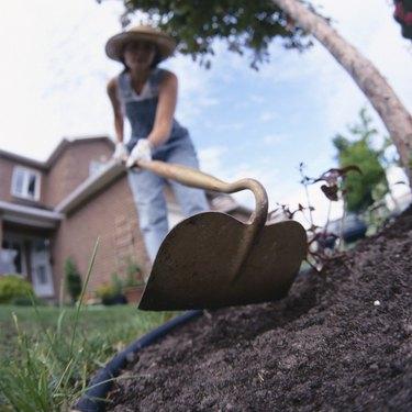 Woman using hoe in soil