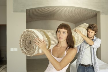 Couple carrying carpet