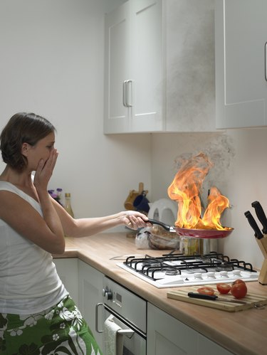 """""""Woman with hand to face holding burning frying pan in domestic kitchen, side view"""""""