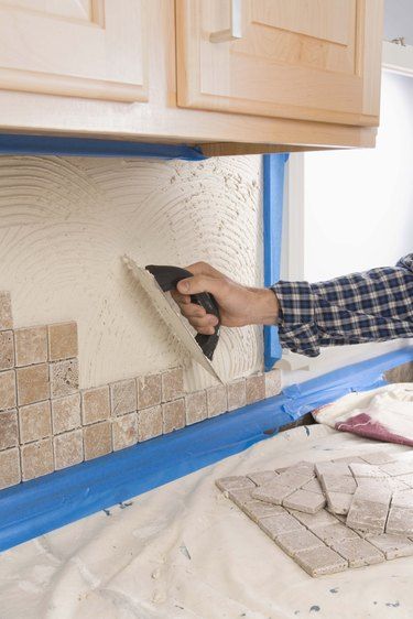 Person putting grout on wall with trowel