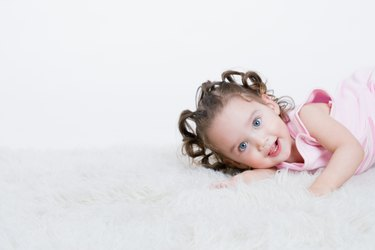Studio shot of toddler on plush rug