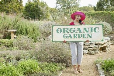 Woman with an organic garden sign