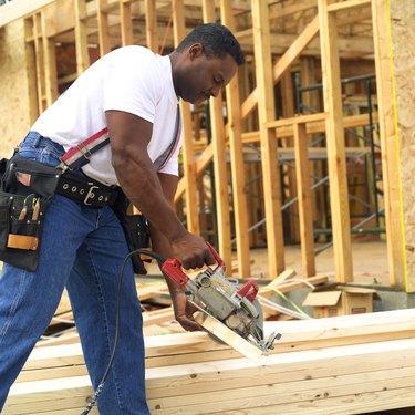 Construction worker cutting lumber