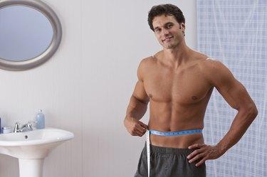man mesuring waistline