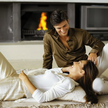 A young woman lying on a rug talking to a young man sitting beside her