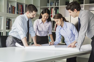 Four architects standing and planning around a table while looking down at blueprint