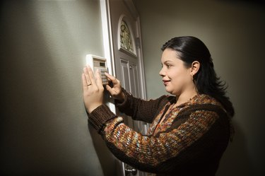 Woman setting house alarm