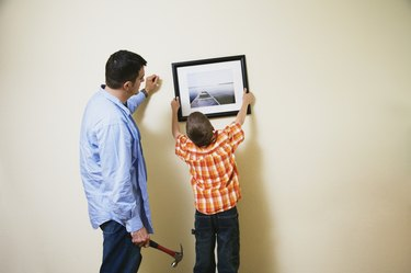 Father and son hanging picture together