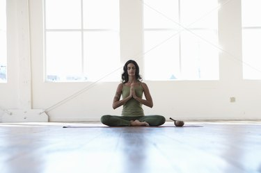 Young woman sitting in lotus position, meditating, eyes closed