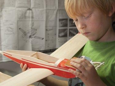 Boy building wooden model airplane