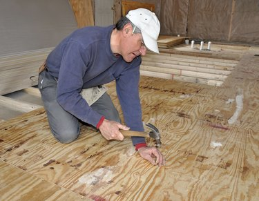 Man nailing down plywood sub-floor