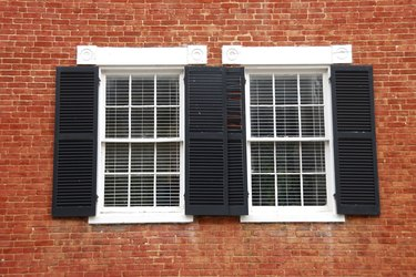 Windows with Black Shutters on Red Brick House